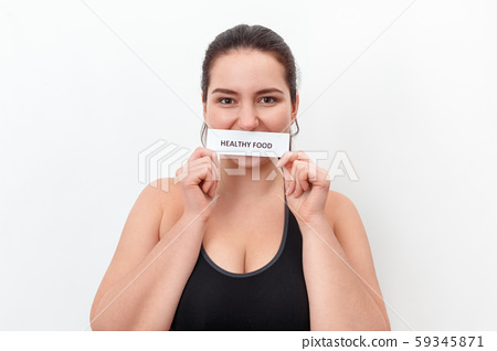 Body Care. Chubby girl standing isolated on white covering mouth with healthy food paper smiling 59345871