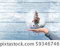 Human hand holding decorated Christmas tree 59346746