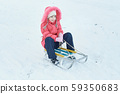 Girl sledding in the park in winter 59350683