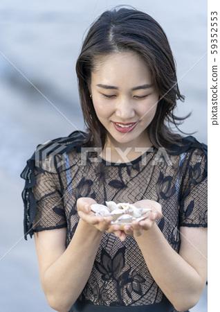 撿貝殼在海灘上的年輕女子的生活方式 59352553