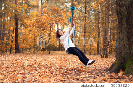 Happy woman on a swing in the autumn forest 59352829