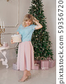 Young woman decorates Christmas tree with Christmas toys 59356720