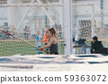 Pole vaulting indoors - young sportive woman with ponytail running with a pole in her hands 59363072