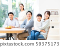 A smiling three generation family gathering at the dining room 59375173
