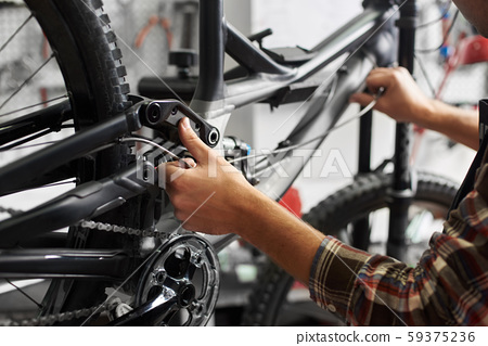 Male mechanic working in bicycle repair shop using tools 59375236