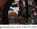 Male mechanic working in bicycle repair shop using tools 59375289