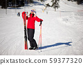 Winter holiday and sport concept with woman with skis in her hands at the foot of the mountain 59377320