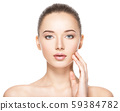 Young woman with healthy clean skin touches the 59384782