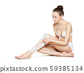 beautiful young woman depilating legs by waxing 59385134