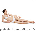 Beautiful woman with perfect body lying on white 59385179