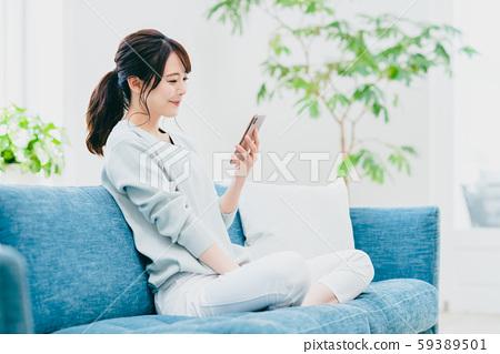 一個年輕的女人,在客廳裡操作智能手機 59389501