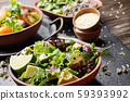 Clay dish with salad of avocado, green and violet 59393992