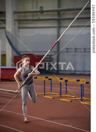 Pole vaulting - pretty woman is warming with long pole 59396447
