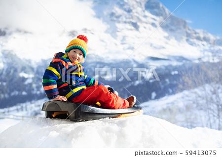 Boy on sled ride. Child sledding. Kid on sledge 59413075
