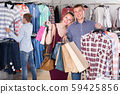 Family stands near clothes and choosing man shirt 59425856