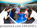 Gambling friends boxing giant gloves on an inflatable trampoline in an amusement park 59426951