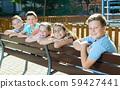 Glad children sitting on a bench 59427441