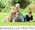 Portrait of big happy family with parents and four children on green lawn outdoors 59427562