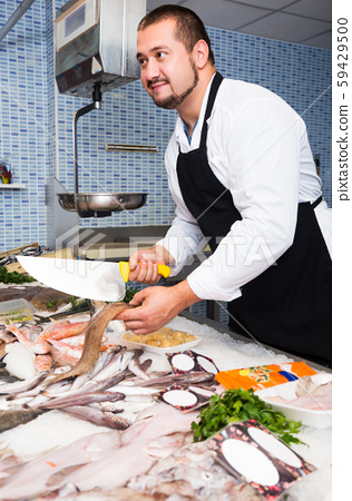Seller with knife cut fish 59429500
