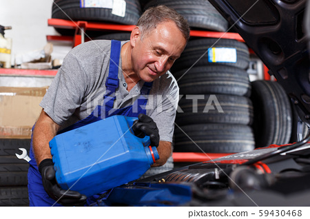 Mechanic checking and replacing motor oil 59430468