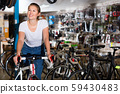 Portrait of girl who is standing with bicycle in store. 59430483