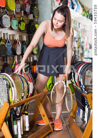 Girl standing in t-shirt in sporting goods store with racket 59430789