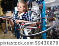 Portrait of girl who is working and replacing wheels with another one in workshop. 59430879