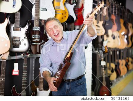 musician demonstrating an electric guitar 59431165