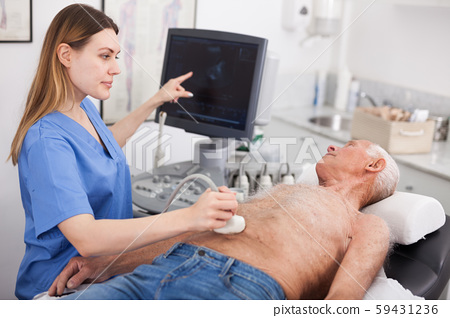 Woman doctor examines a senior man at abdomen with ultrasonic 59431236