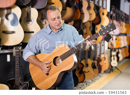 Man is playing on acoustic guitar 59431563