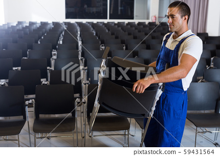 Worker carrying chairs in empty room 59431564