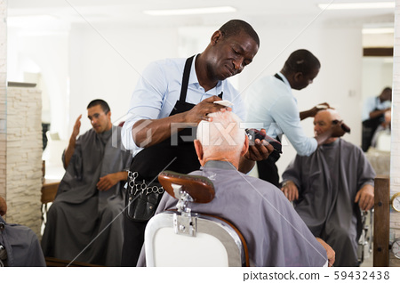 Hairdresser doing styling with hair clipper 59432438