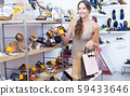 Positive adult woman standing with chosen shoe 59433646