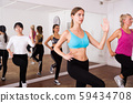 Cheerful different ages women learning swing steps at dance class 59434708