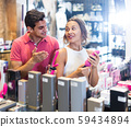 female and male purchasers touching in the modern sex shop different sexy toys 59434894