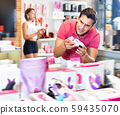 male purchaser touching sexy toys in the modern sex shop 59435070