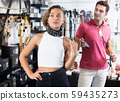 Woman and man purchasers choosing leather collar 59435273