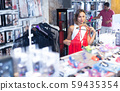 Buyer woman choosing red color clothing in the sex shop 59435354