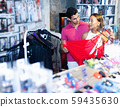 Woman and man buyers choosing color sexy clothing in the sex shop 59435630