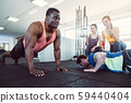 Two men have a push-up competition in the gym with girls cheering 59440404