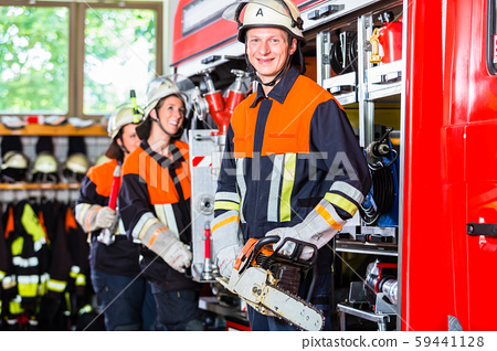 Fire fighters attaching hose at hose laying vehicle 59441128