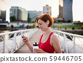 Young woman with smartphone resting after doing exercise on bridge outdoors in city. 59446705