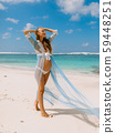 Young pregnant woman in dress expecting baby, posing at tropical beach 59448251