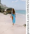 Young pregnant woman in dress expecting baby, posing at tropical beach 59448255