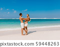 Young pregnant woman with husband at paradise beach. Happy couple at tropical island 59448263
