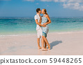 Young pregnant woman with husband at paradise beach. Happy couple at tropical island 59448265