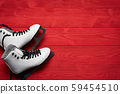 Pair of White Ice Skates on red wooden planks 59454510