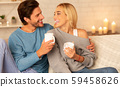 Couple Laughing Drinking Coffee And Talking Sitting On Sofa Indoor 59458626