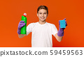 Teenager in protective gloves holding sponge and bottle with detergent 59459563