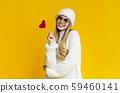 Portrait of flirting winter girl holding red heart card 59460141